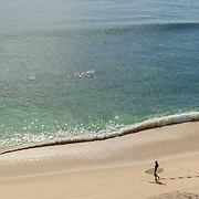 Surfer at Playa Palmilla getting ready. San Jose del Cabo