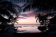 An infinity pool at sunset at the Lux Le Morne Hotel on Le Morne Brabant Peninsula in south west Mauritius, The Indian Ocean