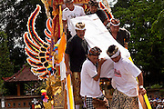 Apr. 25 -- UBUD, BALI, INDONESIA:  Cokorde Gede Raka's coffin is carried out of the funeral tower at his cremation. Cokorde, a member of Ubud's royal family, was cremated Sunday, Apr. 25. Balinese are Hindus and cremate their dead. Balinese funerals are elaborate - and expensive - affairs. A funeral for one person costs a minimum of 45 million rupiah (about $5,000 US). The body is placed into the bull's body at the cremation and cremated in the bull. The funeral pyre is burnt adjacent to the bull. That is what a family may earn in two to three years. The result is that only the rich can afford formal cremations. The body (in the casket) is placed in the top of the funeral pyre and the procession takes the body to the cremation site. The funeral pyre, and the body, are spun at intersections to confuse the spirits so the soul doesn't try to return to its home and to confuse evil spirits.    PHOTO BY JACK KURTZ