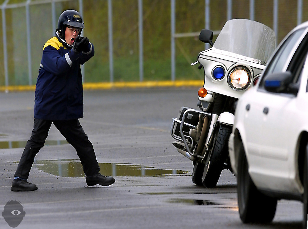 Portland Police officer Jeff Niiya simulates drawing his weapon on a reversing vehicle during motorcycle training at the Port of Portland.