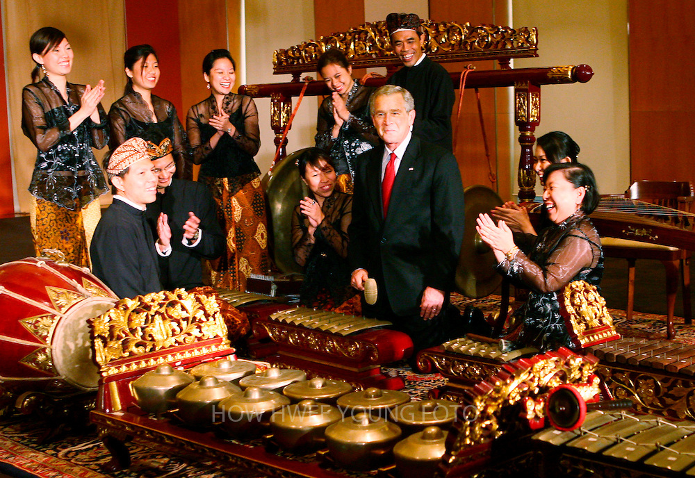 epa00863533 Performers applaud U.S. President George W. Bush (C) after he played the saron in an Indonesian traditional Gamelan orchestra during a tour of the Asian Civilisation Museum in Singapore on Thursday 16 November 2006. Bush arrives in Singapore Thursday while enroute to attend the annual Asia-Pacific Economic Cooperation (APEC) summit in Vietnam.  EPA/HOW HWEE YOUNG