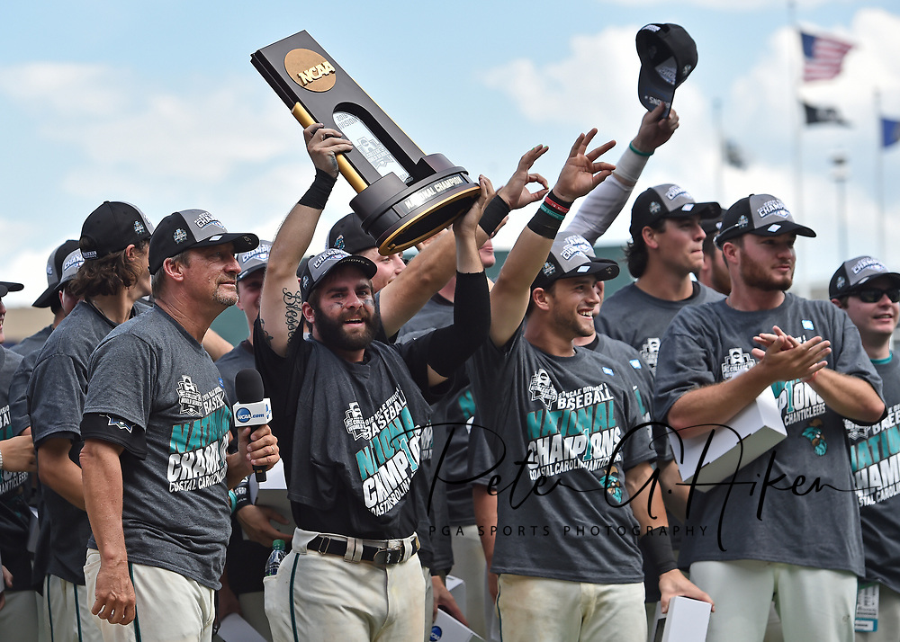 Head coach Gary Gilmore (L) and player Anthony Marks (C) of the Coastal Carolina Chanticleers celebrate with the team after defeating the Arizona Wildcats 4-3 for the National Championship at the College World Series Championship Series at TD Ameritrade Park in Omaha, Nebraska.