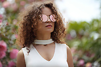 Fashion portrait of a beautiful young stylish woman wearing cat eye shaped mirror sunglasses and a white v-neck open cleavage top in outdoor summer scenery