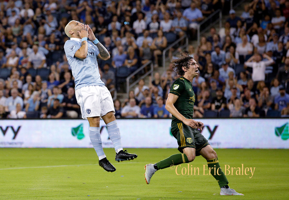 Sporting Kansas City midfielder Yohan Croizet, left, reacts after missing a goal kick as Portland Timbers defender Zarek Valentin, right, defends during the second half of a MLS soccer match in Kansas City, Kan., Saturday, Aug. 18, 2018. (AP Photo/Colin E. Braley)