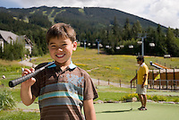 A family plays a round of mini-golf at the Adventure Zone, Blackcomb Mountain, Whistler, BC Canada.