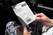 A middle-aged lady checks her test receipt card from the driver's seat of her car after handing over a self-administered Coronavirus (COVID-19) test in south London. There are four steps to the self-administered Covid-19 test (inserting a swab into the nose and throat) which the public works through in their car, windows up and all communications with army personnel via phone, in a south London leisure centre, on 2nd June 2020, in London, England. The kit provided consists of a booklet, plastic bag, swab, vial, bar codes and a sealable biohazard bag. The swab sample is taken from the back of the throat and nasal passage with the contents sealed and returned to soldiers through a narrow window. The whole process takes between 5-10mins with results available with 48hrs.
