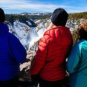 Clients admire the view of the Grand Canyone of the Yellowstone River in winter.