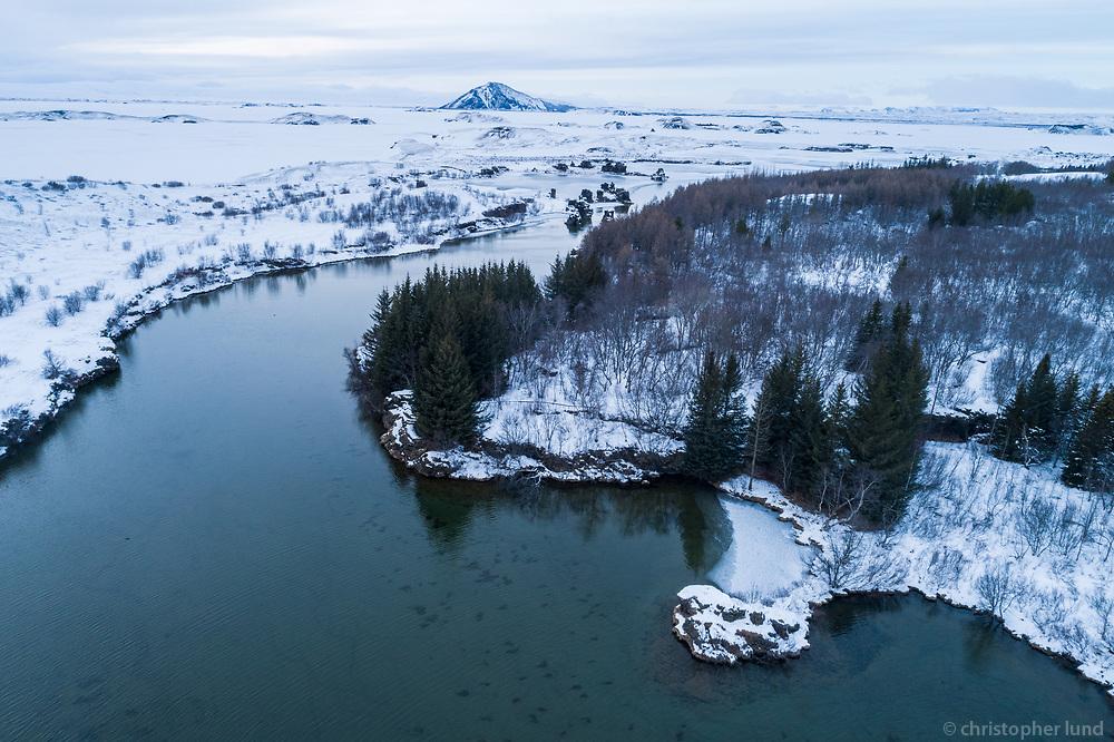Höfði and Kálfastrandavogar at Lake Mývatn. Winter aerial drone shot. North Iceland.