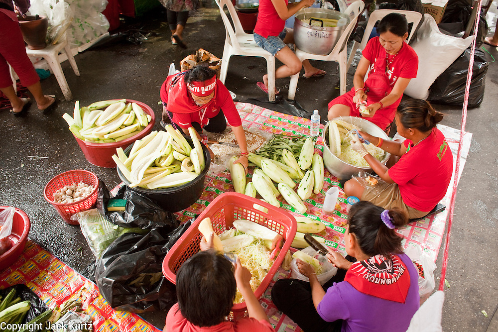 """18 APRIL 2010 -- BANGKOK, THAILAND: Women shred papaya to make """"som tam"""" (papaya salad) at a Red Shirt cafe near the protest venue. The Red Shirts protest in the Ratchaprasong Shopping district, home to Bangkok's most upscale malls, is costing the Thai economy millions of Baht per day because the malls and most of the restaurants are closed and tourists are staying away from the area. But that hasn't stopped the Red Shirts who have brought their own economy with them. There are Red Shirt restaurants, food stands, souvenir vendors and more, creating a micro economy for Red Shirts in the area.  The Red Shirts continue to occupy Ratchaprasong Intersection an the high end shopping district of Bangkok. They are calling for Thai Prime Minister Abhisit Vejjajiva to step down and dissolve the parliament. Most of the Red Shirts support ousted former Prime Minister Thaksin Shinawatra.   PHOTO BY JACK KURTZ"""