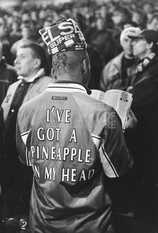 Football fan wearing a strip printed with 'I've got a pineapple on my head'
