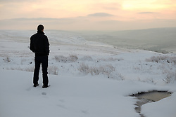 © Licensed to London News Pictures. <br /> 27/12/2014. <br /> <br /> Castleton, United Kingdom.<br /> <br /> A motorist stops to take in the view as he looks out over the snow covered North Yorkshire Moors after overnight snowfall caused disruption in some parts of the country.<br /> <br /> Photo credit : Ian Forsyth/LNP