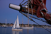 USA, Newport, RI - Side view of sail boat's bow in front of harbor at dusk. Short focus.