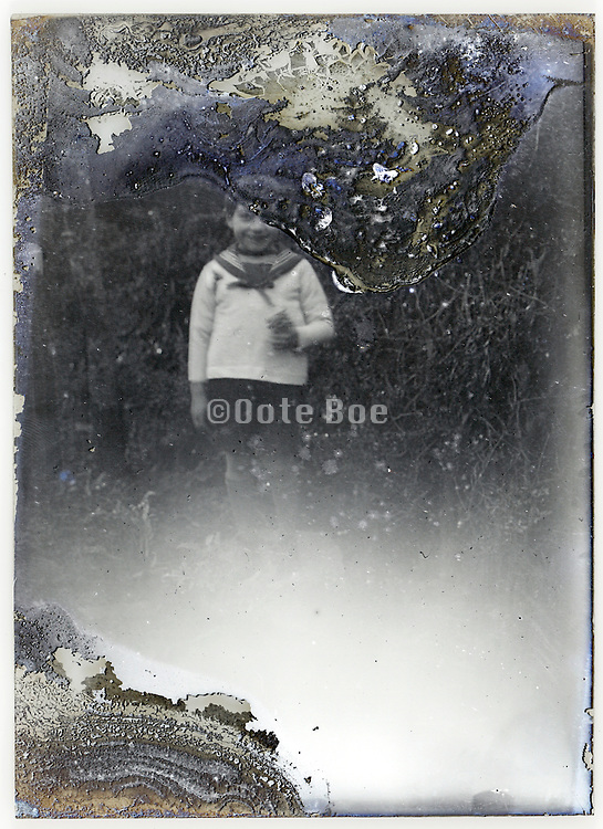 severely eroding glass plate photo with young child standing in garden setting