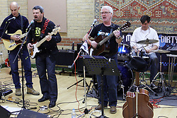 "© Licensed to London News Pictures.  17/12/2011. Buckinghamshire, UK. Martin Davis (pictured 2nd right), lead singer of band Dirty Mavis performs The Oak Tree Lament (Did you stop the HS2), at the Stop HS2 Christmas party in Lacey Green. The protest song against the planned high speed railway between London and Birmingham that would devastate the Chilterns mocks the £17 billion cost as ""a pound for every leaf"".  Martin, a footwear designer and salesmen, wrote the song in under an hour while commuting to work. The single is due to be released tomorrow (Mon 19th) in time for Christmas and bookmakers have quoted odds as low as 16-1 on it being Christmas #1. Half of the proceeds will go towards the Stop HS2 campaign. Photo credit: Cliff Hide/LNP"