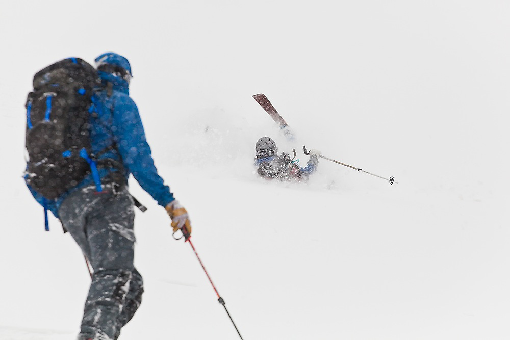 A backcountry skier watches another crash in deep powder below Hayden Peak, San Juan Mountains, Colorado.