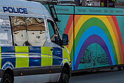 A police van passing a rainbow of how and togetherness on a bread stall on Northcote Road, SW London. The 'lockdown' continues in London because of the Coronavirus (Covid 19) outbreak.
