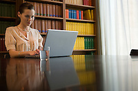 Young woman using laptop at desk in library