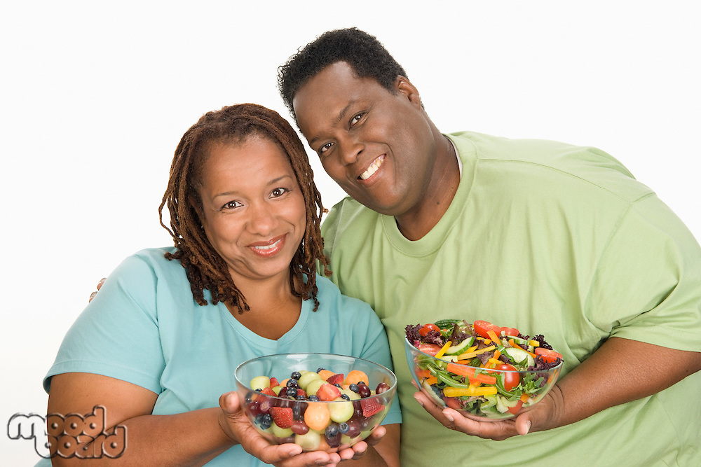 Mid-adult overweight  woman and mid-adult overweight man holding bowls with fruit and vegetable salad, smiling