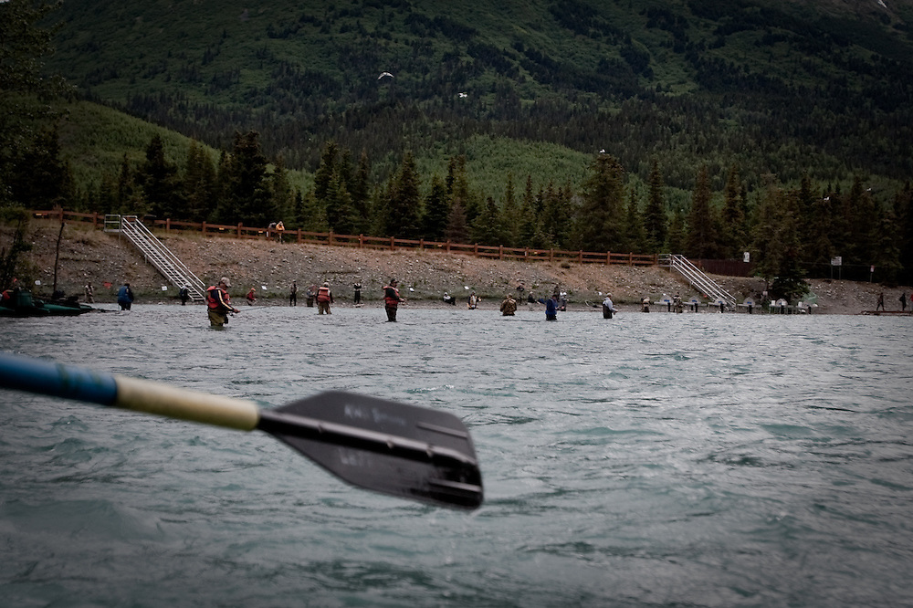 Anglers engage in combat fishing along the banks of the Kenai River, one of the world's most productive salmon streams, Alaska.  Suspended glacial silt gives the river it's distict emerald color.