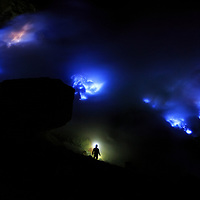 "A lone miner considers his next point of extraction as the ""blue fire"" rages above at Ijen Volcano, Indonesia, 2013"