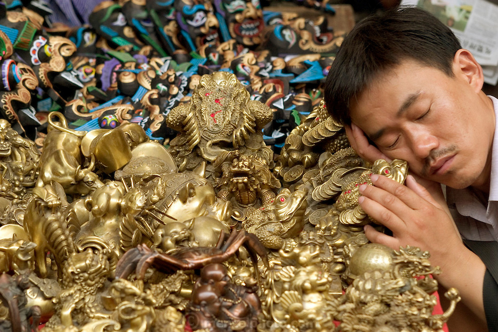 A vendor takes a nap on his brass good luck frogs at Beijing's Panjiajuan weekend antique/flea market. China. (Supporting image from the project Hungry Planet: What the World Eats)