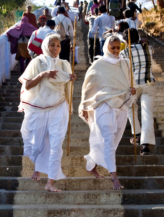 pilgrims wearing white and traditionally descend the stairs running in bare feet.