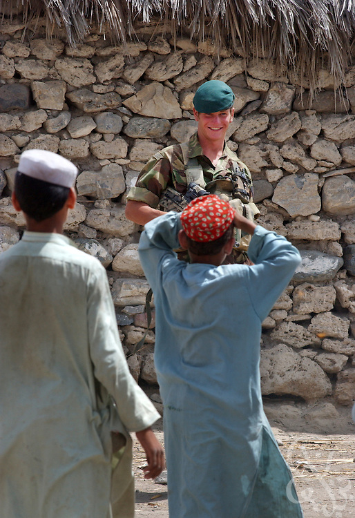 A British Marine commando jokes with Afghan children June 18, 2002 during Operation Buzzard in southeastern Afghanistan. Britain is expected to begin withdrawing its 1,700 troops currently deployed in Afghanistan by the end of June 2002