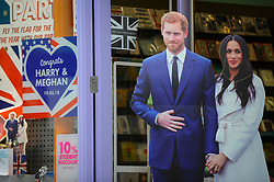 © Licensed to London News Pictures. 11/05/2018. WINDSOR, UK. Cardboard cut-outs of the Royal couple decorate a shop doorway as preparations continue in Windsor for the upcoming wedding between Prince Harry and Meghan Markle on 19 May.  Thousands of people are expected to visit the town for what has been billed as the wedding of the year.  Photo credit: Stephen Chung/LNP