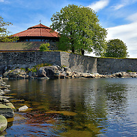 Christiansholm Fortress on Waterfront in Kristiansand, Norway <br /> When the Christiansholm Festning was built circa 1672, it stood on a small island off the shore of Kristiansand in the East Harbor. A tall, stone bastion still surrounds its base. The garrison was only tested in battle during the Napoleonic Wars when it was attacked in 1807 by two Royal Navy ships including the HMS Spencer. When the British succeeded in occupying the fort, they tried to destroy it with dynamite. Their plan literally backfired when a delayed fuse unexpectedly exploded, killing four seamen.