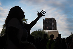 © Licensed to London News Pictures. 14/08/2017. London, UK. A woman speaks under the A40 flyover - in sight of the remains of Grenfell tower after marching in silence to remember the victims of the fire.  The silent march takes place every month to remember the 80 residents of the 24 storey tower block that died in the tragedy on June 12, 2017 in Kensington. Photo credit: Peter Macdiarmid/LNP