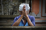 An elderly Balinese man rests against a wall in Goa Gajah temple and holds his hands together in prayer. Over 90% of the Balinese population is devoted to Balinese Hinduism which is rich in rituals and arts.