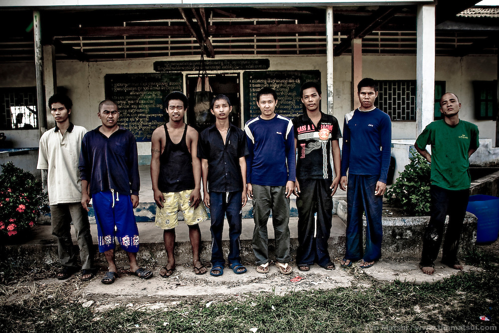 Residents of the only government-run drug rehabilitation center in Cambodia stand outside their old dormitory at the Military Police base in Koh Kong. The center has treated some migrants returning from the Thai fishing industry where they were exploited and grew addicted to drugs. Established at the request of the provincial governor, the Ministry of Social Affairs now supports the center where the military provides limited education, sports, and labor; both residents and soldiers grow their own produce to supplement their diet. Deputy Commander Keo Vichet stated the program is under-funded and the soldiers are doing their best considering they have no training in drug rehabilitation.