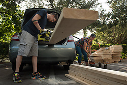 September 8, 2017 - Delray Beach, Florida, U.S. - Jacob Puusalu and his wife Danielle, right, cut 2x6's in a Home Depot parking lot to be able to fit them in their car to take home and board their apartment in Delray Beach, Fla., Sept. 08, 2017. Irma's tracking has shown her to make landfall on southern Florida coast by this weekend. (Credit Image: © Ken Cedeno via ZUMA Wire)