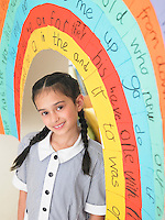 Elementary schoolgirl standing under painted arch in classroom portrait