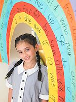 Elementary schoolgirl standing under painted arch in classroom portrait