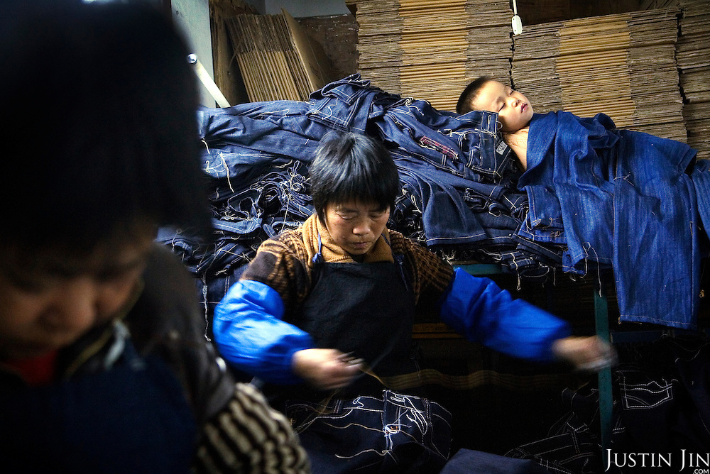 "Workers sew jeans in Mr Huang's factory in Zhongshan city, China, while a child sleeps on a pile of jeans. .This picture is part of a photo and text story on blue jeans production in China by Justin Jin. .China, the ""factory of the world"", is now also the major producer for blue jeans. To meet production demand, thousands of workers sweat through the night scrubbing, spraying and tearing trousers to create their rugged look. .At dawn, workers bundle the garment off to another factory for packaging and shipping around the world..The workers are among the 200 million migrant labourers criss-crossing China.looking for a better life, at the same time building their country into a.mighty industrial power."