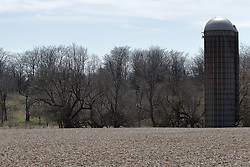 A steel topped concrete grain storage silo stands at the back of an unplanted field near a tree line.