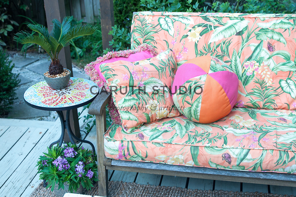 Outdoor furniture with tropical print cushions
