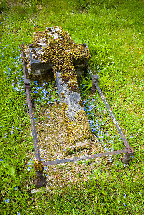 An ancient moss-covered cross on a grave in a traditional church graveyard in England
