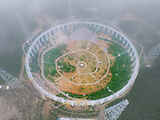 China is building the world's biggest radio telescope that's the equivalent of 30 football pitches so it can 'listen to the UNIVERSE'<br /> <br /> China is building the world's largest radio telescope in Guizhou province, south west China.<br /> <br /> Construction for the Five hundred metre Aperture Spherical Telescope, shortened to FAST, started in March 2011. The project is now expect to be completed by September 2016.<br /> <br /> The gigantic radio telescope will cost approximately 1.2 billion Yuan (£120 million), making it the biggest astronomy project China has ever had. <br /> <br /> It will allow scientists to get weaker radio signals from outer space, even further than our solar system,<br /> Li Di, the chief scientist of the National Astronomical Observatories Chinese Academy of Sciences, said: 'FAST will remain the best in the world in the next twenty to thirty years after it is completed.'<br /> <br /> The idea of building this radio telescope was first proposed in 1993. <br /> <br /> But it was only approved in 2006 after an international review and advisory conference on the science and technology of FAST.<br /> <br /> It has been described as 'ears' and will help scientists listen to the universe.<br /> Scientists from different fields, including physicists, geologists and astronomers, welcomed the construction of the new telescope as it will boost the human capacity to observe outer space.<br /> <br /> Chen Xuelei, a physicists said that the data can help prove Einstein's relativity theory once more data of gravitational waves can be retrieved from the telescope.<br /> <br /> Li Di added: 'FAST can answer questions not only limited to astronomy but questions about humanity and nature. The scientific potential of this telescope is hard to predict.' The telescope is made up of 4,450 reflective panels. The size of the dish will be about thirty football pitches.<br /> <br /> Cables are attached to every reflective panels to control its coordinates.<br /> <br /> The intricate design allows scientists to shift the dish to receive radio signals from different angles.<br /> <br /> Li Di said : �