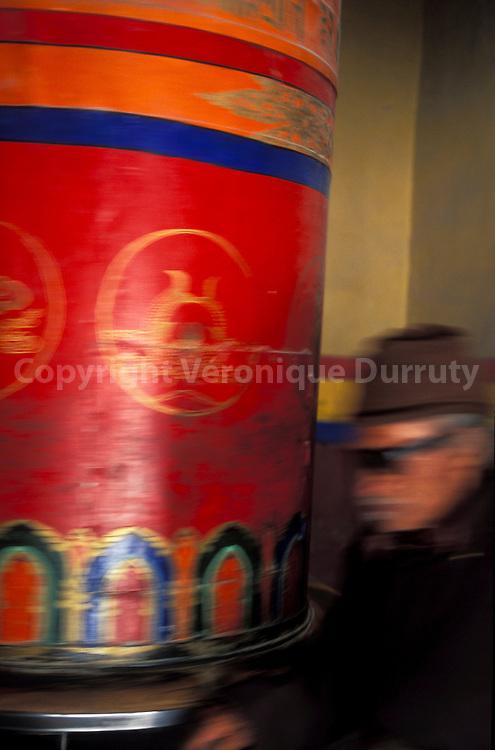 This man is walking around the prayers wheel according to the Tibetan buddhism tradition.