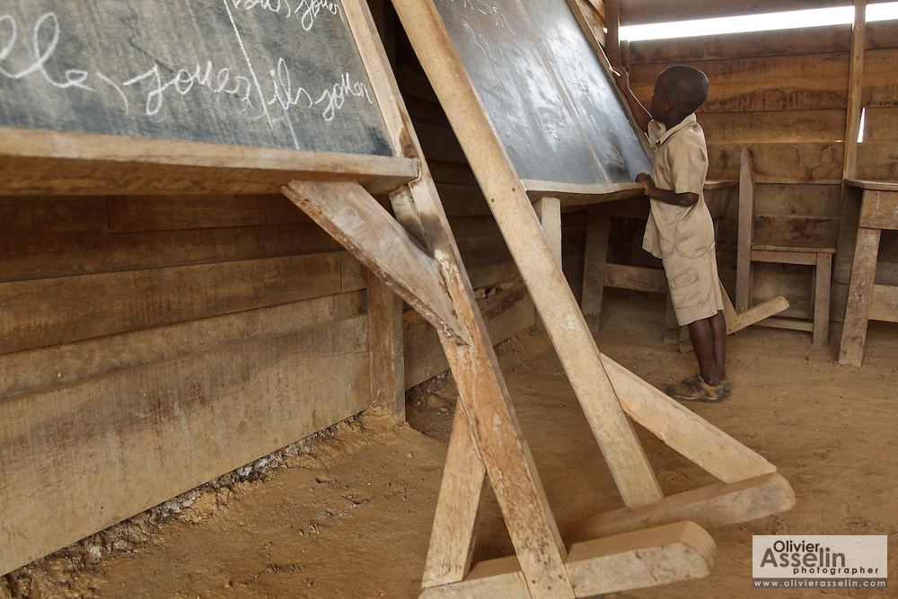 A boy writes on a blackboard during class at the Podio primary school in the village of Podio, Bas-Sassandra region, Cote d'Ivoire on Friday March 2, 2012. The blackboards are resting against the wall because the floor isn't level, and they would otherwise fall down.