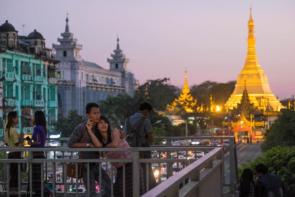 A young couple enjoying the city view from a bridge near the famous Sule Pagoda of Yangon, Myanmar. <br />