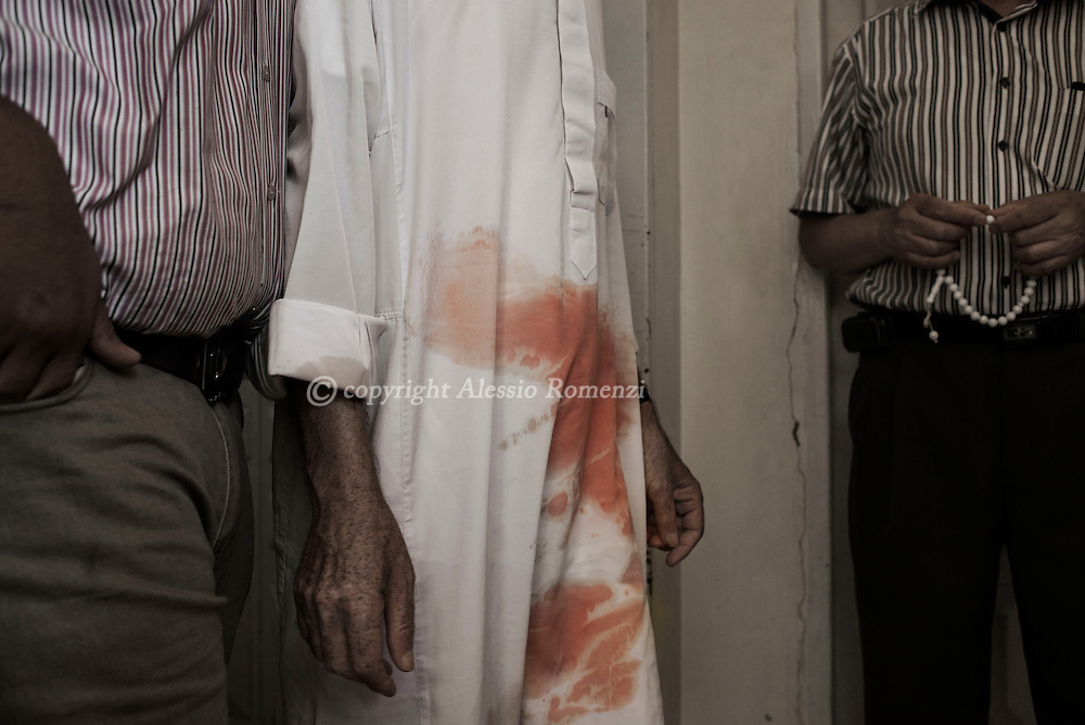 Gaza Strip, Gaza City: A man with blood stains on his jalabiya is seen inside the Al Shifa hospital morgue in Gaza City on July 9, 2014. ALESSIO ROMENZI