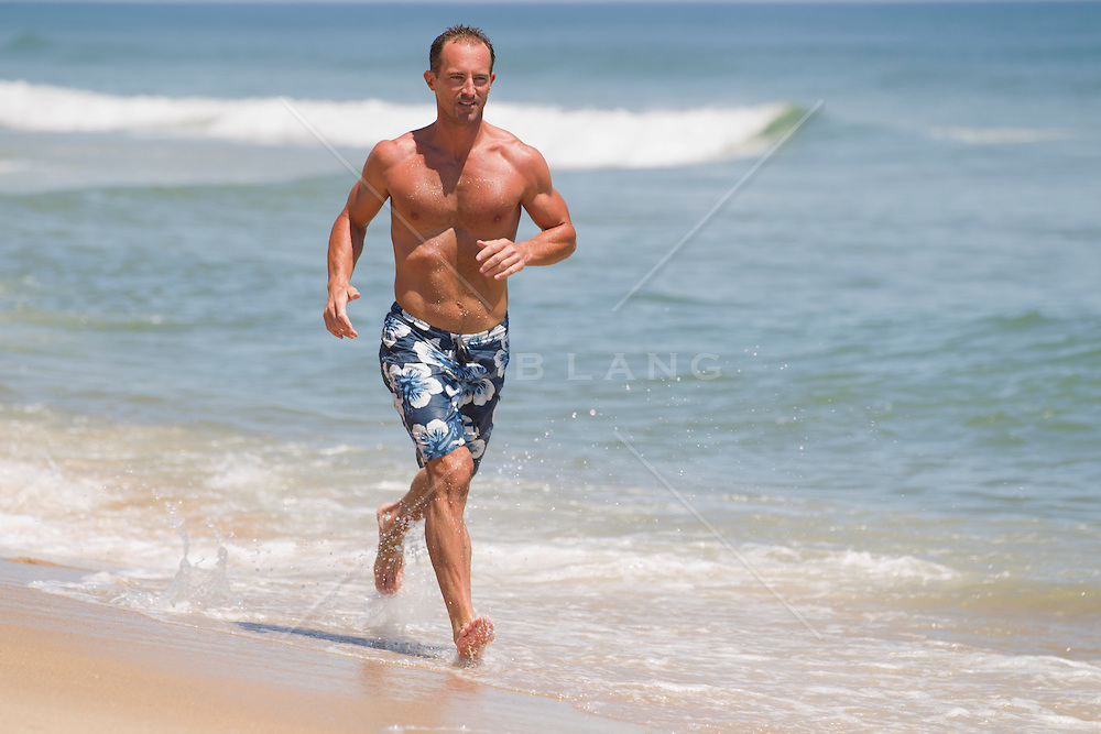 good looking man running on the beach in East Hampton, NY