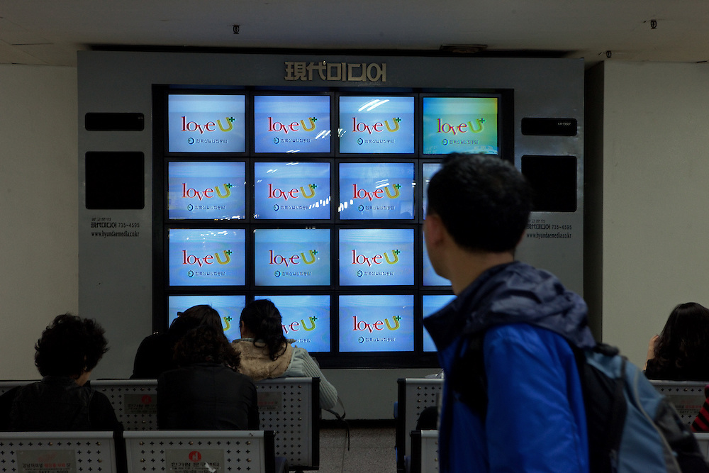 Fernseh Bildschirme und wartende Reisende im Express Bus Terminal im Zentrum der koreanischen Hauptstadt Seoul. <br /> <br /> Television screens and waiting travellers at the Express Bus Terminal in the city center of the Korean capital Seoul.