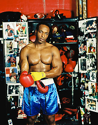 Boxer putting on a red glove by a locker