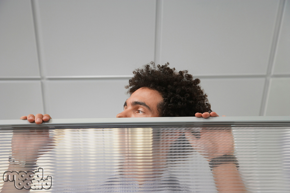 Office worker peering over cubicle wall