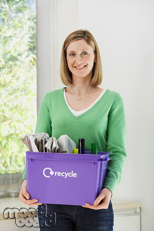 Mid-adult woman holding recycling container smiling