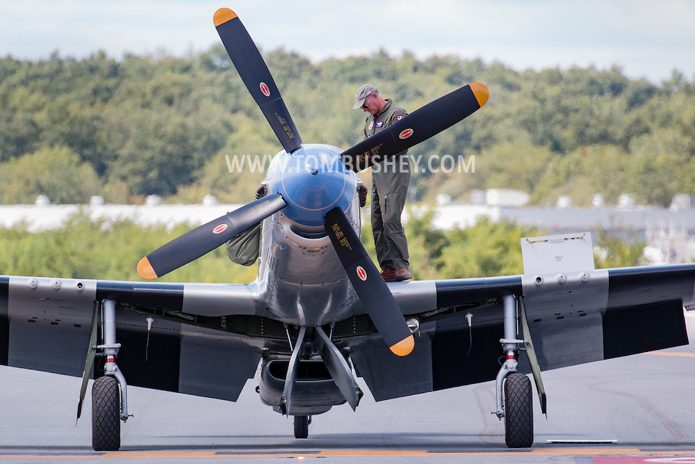 New Windsor, New York - A pilot stands on the wing of a A World War II P-51D Mustang before flying at the New York Air Showat Stewart Airport on Aug. 28, 2015.